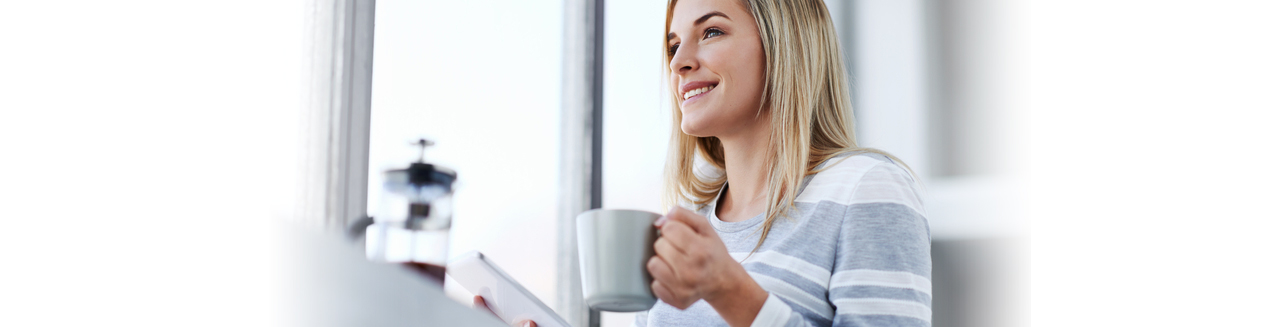 Smiling woman with a tablet and cup of coffee